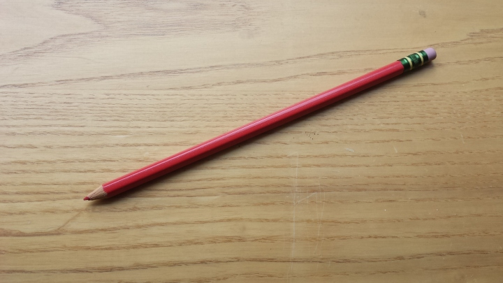 Red pencil on desk.